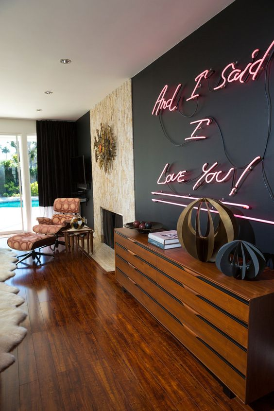 a black accent wall accented even more with a pink neon sign is a pretty and fresh idea that gives a modern feel to the space