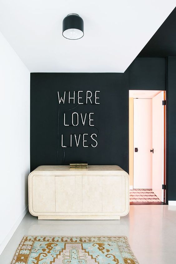 a black accent wall with a neon sign and a gorgeous refined sideboard that resembles a clutch for a wow look