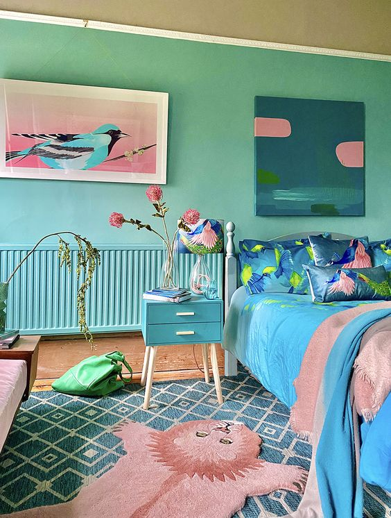 a blue and green bedroom with turquoise walls, a blue nightstand, a bed with pink and blue bedding and lovely artworks