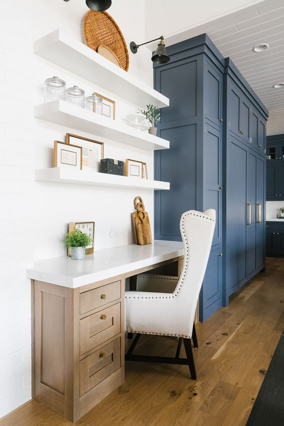 a blue kitchen with shaker style cabinets and a stained desk plus floating shelves and a refined white chair is very stylish