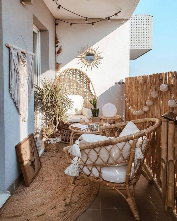 a boho summer balcony with a jute rug, rattan furniture, lamps, an artwork, macrame and potted plants is beautiful and welcoming