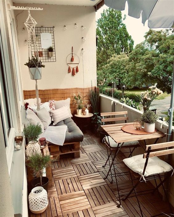 a boho summer balcony with a pallet daybed, small folding furniture pieces, candle lanterns, potted plants and a macrame pot hanger