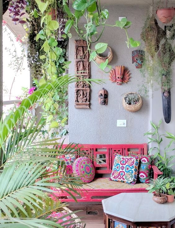a boho summer balcony with a pink bench, a geometric table, a gallery wall of masks and potted plants and greenery