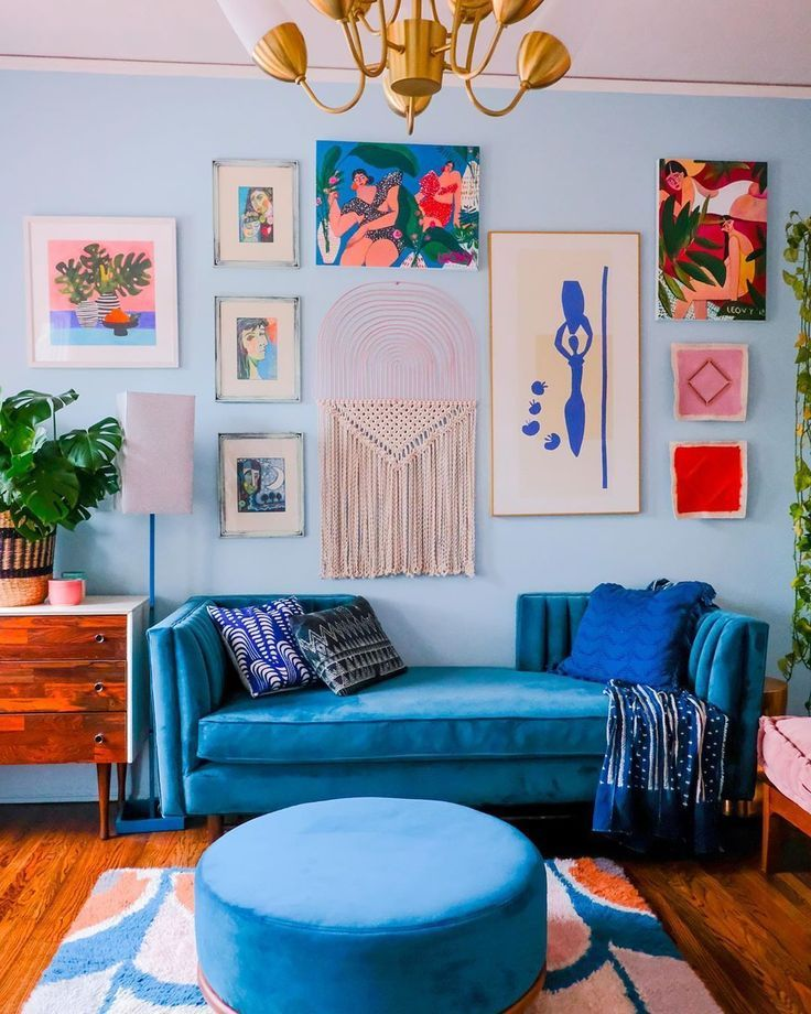 a bold and chic living room with pale blue walls, bold blue seating furniture, a stained dresser, a bright gallery wall and a retro chandelier