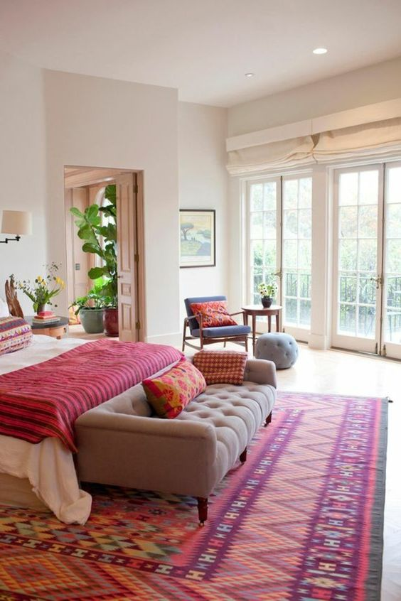 a bold bedroom with a colorful printed rug, a bold blanket and pillows that make this space super colorful