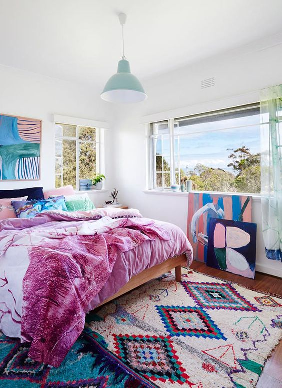 a bold bedroom with a colorful rug, bold bedding and lovely and bold artworks that create a mood in the room