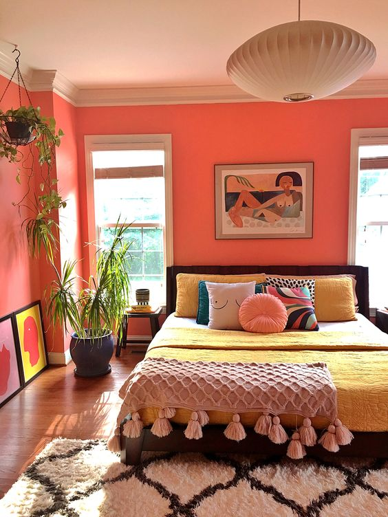 a bold bedroom with coral walls, a dark bed with colorful bedding, a tassel blanket, colorful artworks and potted plants