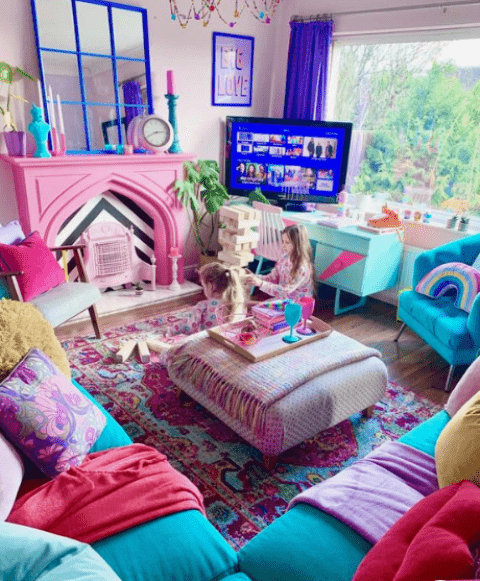 a bold living room with a blue sofa, colorful pillows, a pink fireplace, a mirror in a blue frame and bold textiles