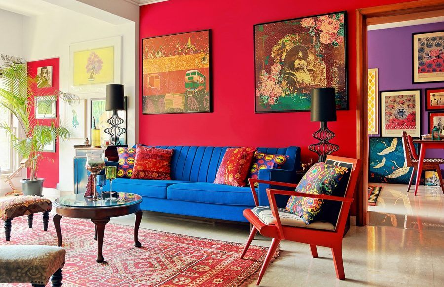a bold living room with a red accent wall, an electric blue sofa, a red chair and a red printed rug plus bright artworks
