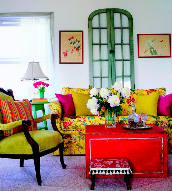 a bold living room with a yellow floral sofa, a refined yellow chair, a red box, floral artworks and green touches here and there