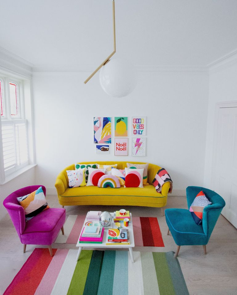 a bold living room with a yellow sofa, a blue and a fuchsia chair, a bright gallery wall and two bold striped rugs