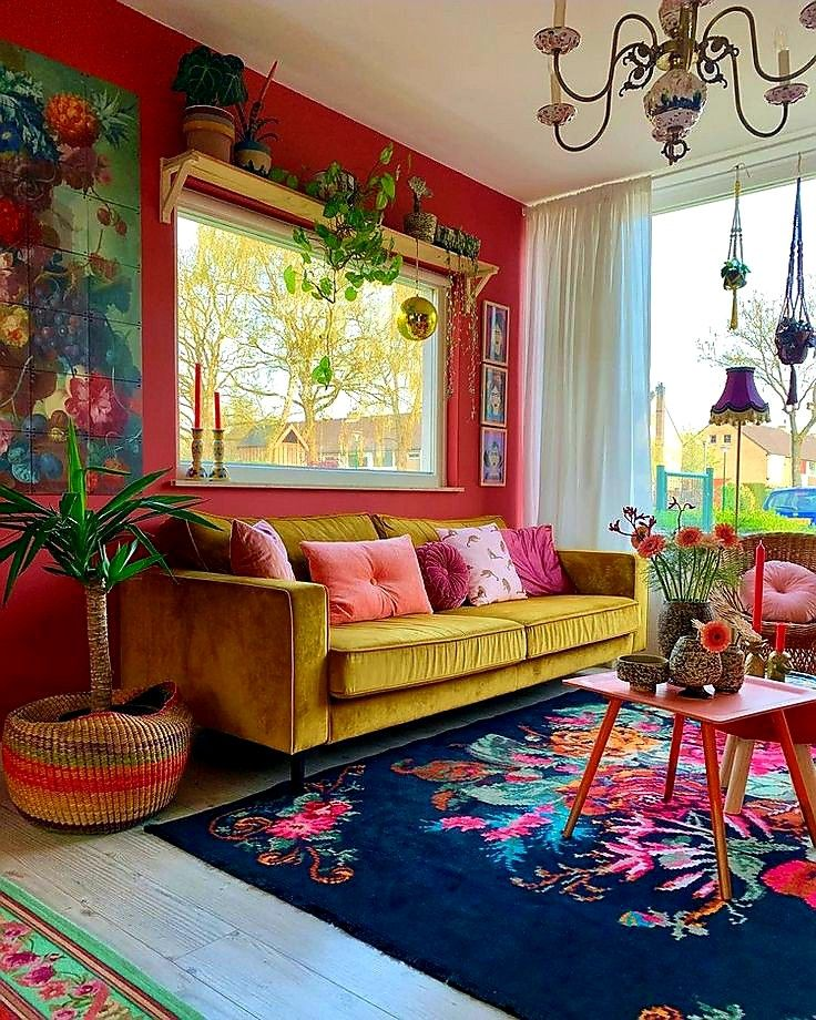 a bold mid century modern space with a red accent wall, a yellow sofa, a colorful floral rug, lots of potted plats and a vintage chandelier