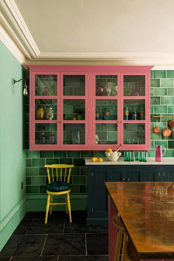 a bright and chic kitchen with green walls, green tiles, navy lower cabinets and pink upper ones plus a yellow chair wows with its colors