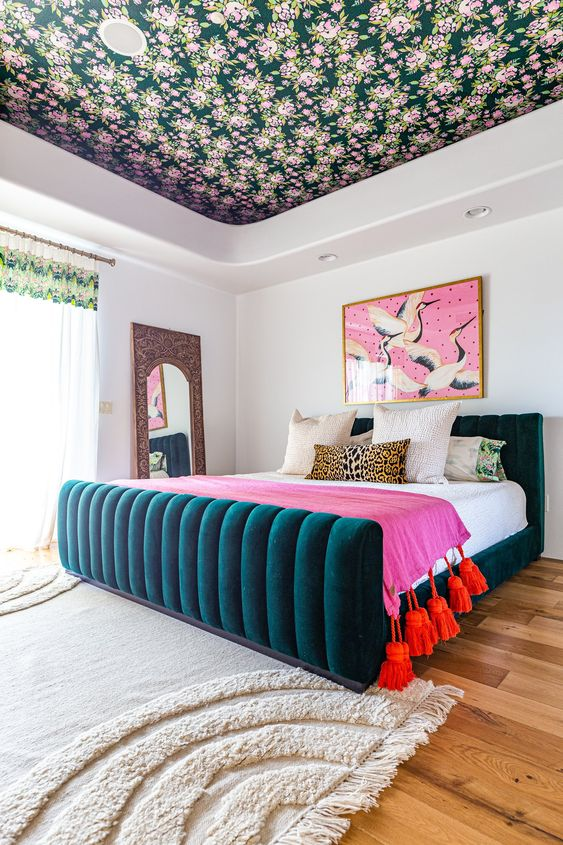 a bright bedroom with a florla ceiling, a teal upholstered bed, bright bedding, a colorful artwork and a mirror in a carved frame