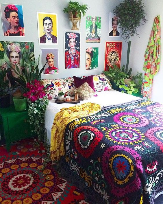 a bright boho bedroom with bold rugs, bedding, printed pillows, potted plants and blooms and a Frida Kahlo inspired gallery wall