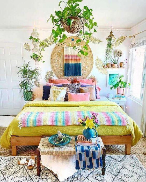 a bright boho bedroom with colorful bedding and pillows, a bold artwork and colorful macrame plus bright pots