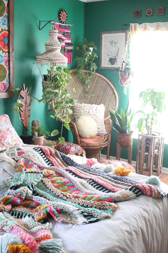 a bright boho bedroom with emerald walls, bold artworks and macrame, colorful bedding and a blanket and lots of potted plants