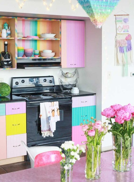 a bright kitchen with colorful cabinets and striped backing for open cabinetry, a pink table and chairs is a fun space