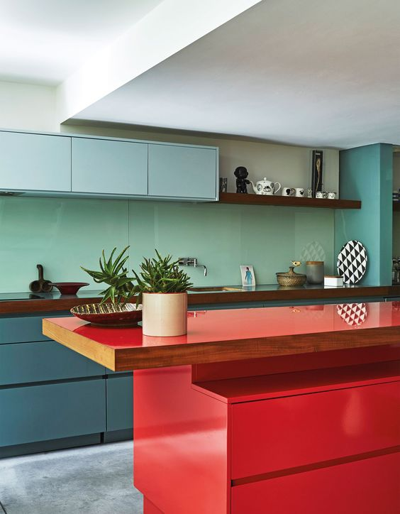 a bright kitchen with navy, light blue sleek cabinets, a mint green backsplash, a red kitchen island and dark stained touches
