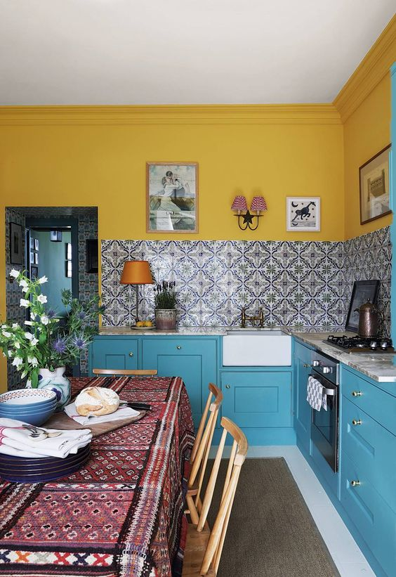a bright kitchen with yellow walls, blue cabinets, a stone countertops and a beautiful printed tile backsplash for a bolder touch