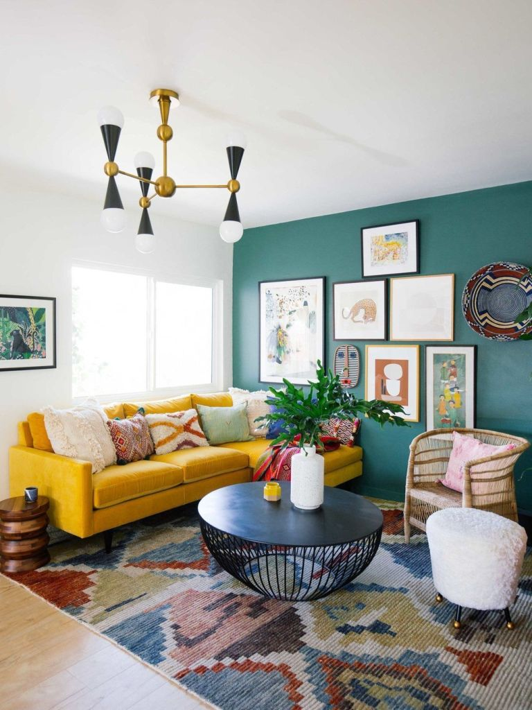 a bright living room with a green accent wall and a gallery wall on it, a sunny yellow sectional, a bright rug and a black table plus some stools