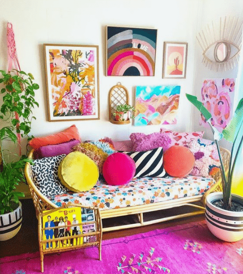 a bright living room with a hot pink rug, a rattan sofa with colorful pillows, a bold gallery wall and potted plants