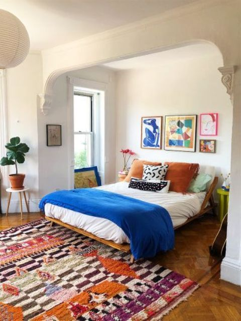 a bright modern bedroom with a colorful rug, bold bedding and a bright gallery wall and potted plants