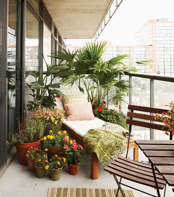 a bright summer balcony with potted plants and blooms, a lounger and small folding furniture pieces