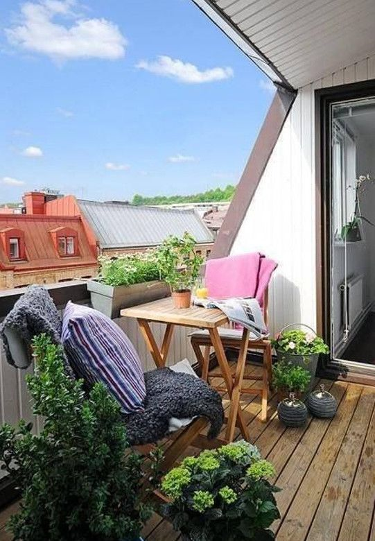 a bright summer balcony with wooden folding furniture, potted greenery and blooms, colorful textiles and a lovely view