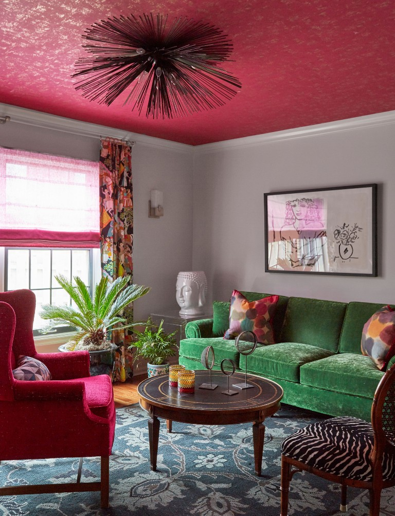 a catchy eclectic living room with a green sofa, a pink chair, curtain and a ceiling, a round table and a zebra print chair
