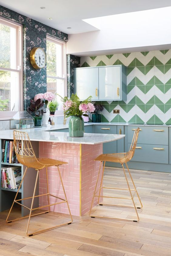 a charming colorful kitchen with grey cabinets, a green and white chevron tile backsplash, floral wallpaper and a pink tile kitchen island and gold stools
