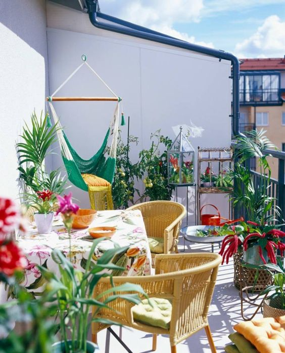 a cheerful and colorful summer balcony with rattan furniture, a hanging chair, potted blooms and greenery and colorful textiles
