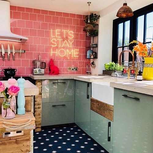 a cheerful kitchen with light green cabinets and a pink tile wall, a neon sign, pendant lamps and a navy star print tile floor