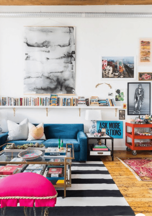 a cheerful living room with a blue sofa, a pink stool, an orange cart, bright artworks and a shelf with books
