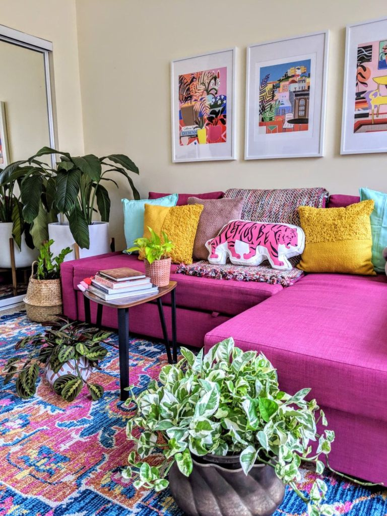 a cheerful living room with a hot pink sectional, colorful pillows and artworks, a bright rug, potted plants and a mirror to add space to it