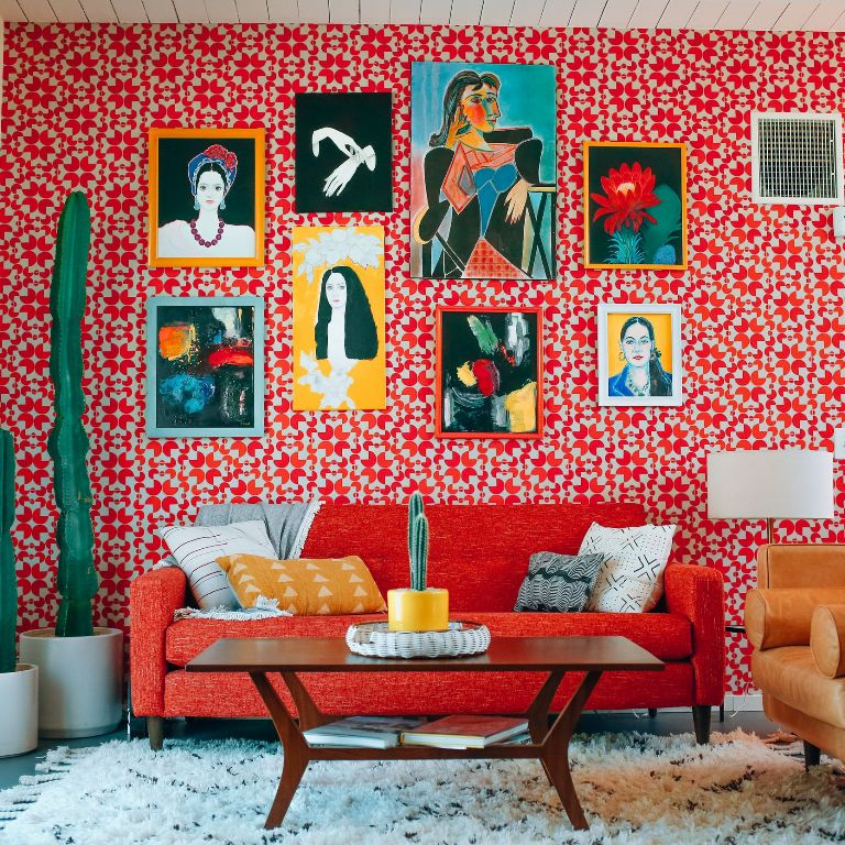a cheerful living room with a red wallpaper wall, a bold red sofa, a gallery wall with bright artworks and potted cacti