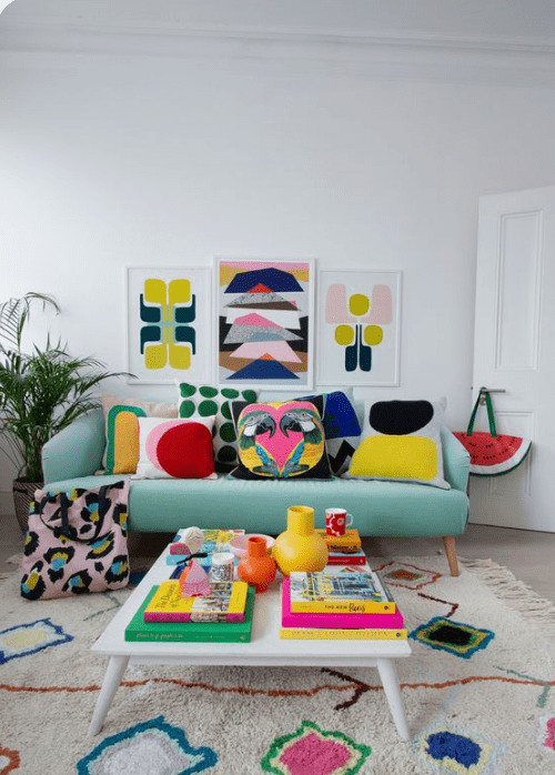 a cheerful lviing room with a mint-colored sofa, a bright gallery wall, pillows, a low table with colorful books and a bold rug