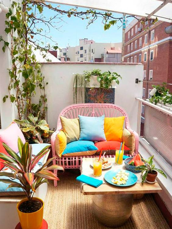 a cheerful summer balcony with a pink loveseat, a bench with pillows, a low table, lots of potted plants and colorful pillows and tableware