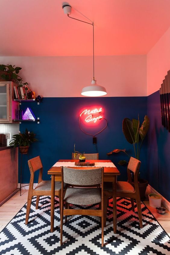 a chic dining space in mid-century modern style, with color block walls, a chic dining set and a pink neon sign for a fun touch