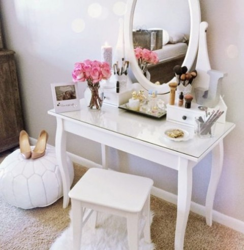 a chic makeup nook with a glass top vanity, a comfy mirror, a stool and a white leather ottoman for creating a girlish feel