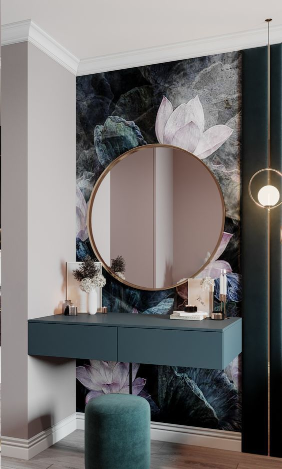 a chic makeup space with a floral wallpaper accent, a teal floating vanity, a green pouf and a large round mirror