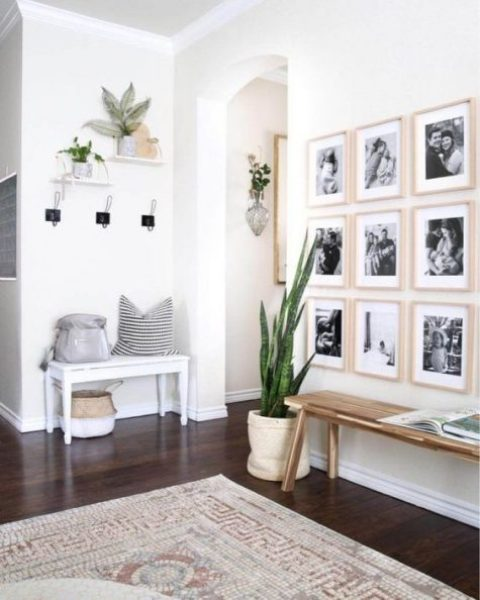a chic modern entryway with a couple of benches, a grid gallery wall, some plants and clothes racks