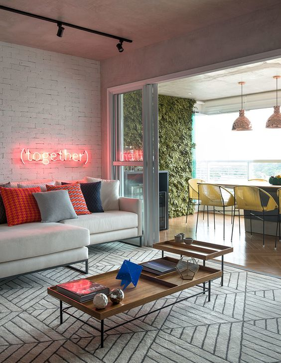 a chic modern living room is highlighted and accented with bright printed pillows and a neon sign over the sofa