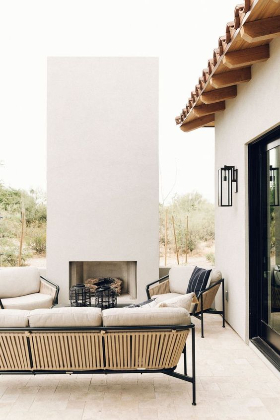 a chic outdoor space with wood and metal furniture, an outdoor fireplace and black candle lanterns is a very stylish area