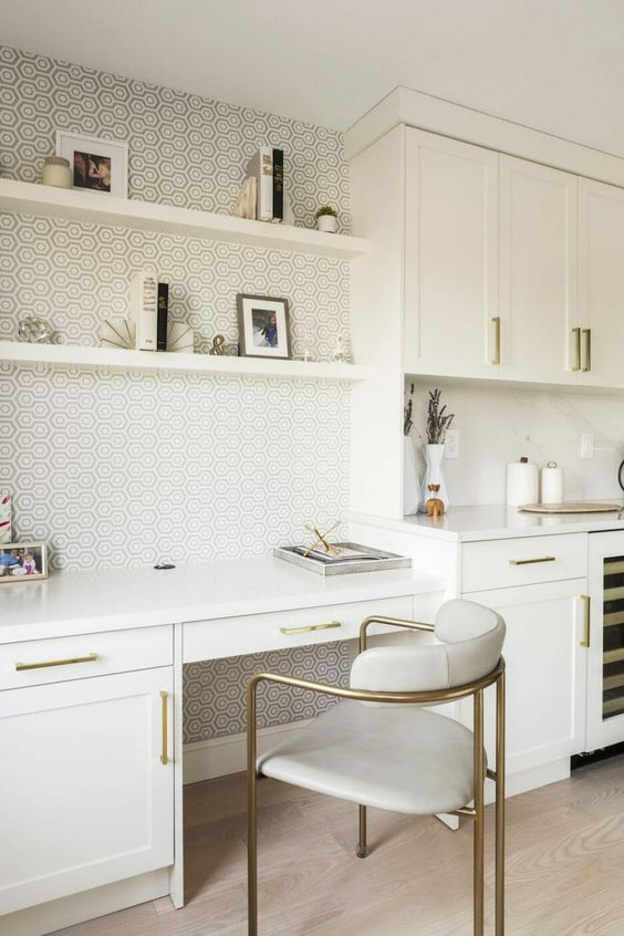 a chic white kitchen and a desk by the cabinet, built-in shelves and backing done with printed wallpaper plus a very refined chair