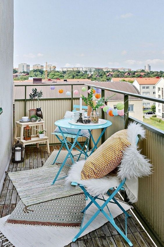 a colorful balcony with folding blue furniture, lovely pillows and faux fur, colorful paper lights and potted plants