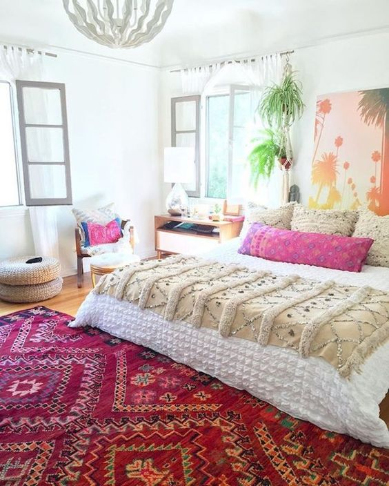 a colorful bedroom with a bold beach artwork, a colorful printed rug, bright pillows that give much color to this space