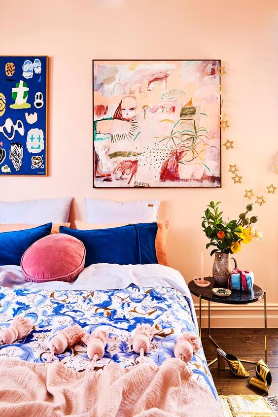 a colorful bedroom with blush walls, a bed with blue and pink bedding, bright artworks is a fun space