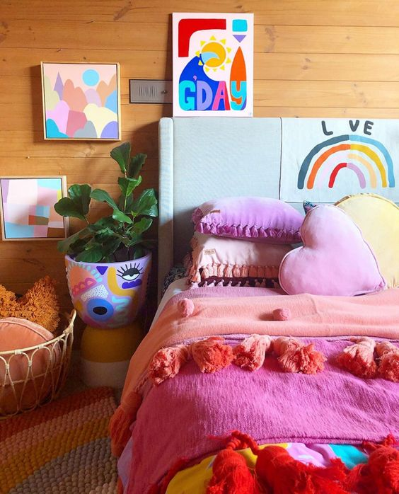 a colorful bedroom with super bright bedding and pillows, a colorful planter with painting and bright artworks on the wall