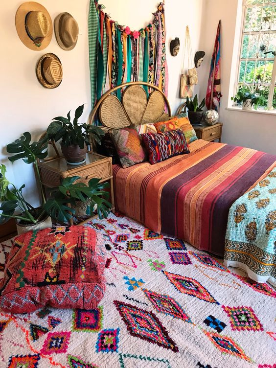 a colorful boho bedroom with bold textiles, pillows, rugs, ottomans and a bunting artwork on the wall is a fun space